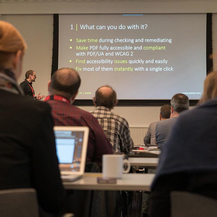 Schulungssituation: im VOrdergrund mehrere Reihen an TeilnehmerInnen, im Hintergrund Markus Erle als Trainer, der gerade darüber spricht, was man mit axesPDF QuickFix alles machen kann